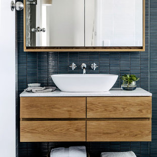 Photo of a contemporary bathroom in Sydney with flat-panel cabinets, medium wood cabinets, blue tile, mosaic tile, blue walls, a vessel sink, grey floor and white benchtops.
