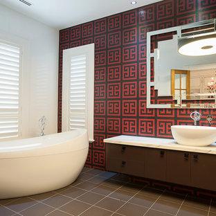 На фото: огромная главная ванная комната в стиле фьюжн с настольной раковиной, фасадами островного типа, коричневыми фасадами, мраморной столешницей, отдельно стоящей ванной, душем над ванной, инсталляцией, красной плиткой, стеклянной плиткой, разноцветными стенами и полом из керамогранита с