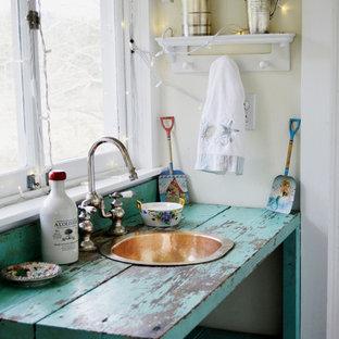 Foto de cuarto de baño principal, campestre, de tamaño medio, con armarios tipo mueble, puertas de armario azules, baldosas y/o azulejos blancos, suelo de mármol, encimera de madera, paredes amarillas y lavabo encastrado
