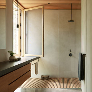 Inspiration for a modern bathroom in Seattle with flat-panel cabinets, concrete floors, granite benchtops, medium wood cabinets, a curbless shower, gray tile, grey floor, an open shower, grey benchtops, a floating vanity and wood.