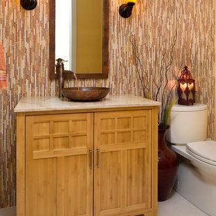 Diseño de cuarto de baño con ducha, asiático, pequeño, con lavabo sobreencimera, armarios tipo mueble, puertas de armario de madera clara, encimera de piedra caliza, sanitario de una pieza, baldosas y/o azulejos multicolor, baldosas y/o azulejos de piedra, paredes amarillas y suelo de piedra caliza