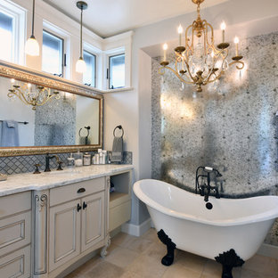 Example of a cottage chic master gray tile beige floor claw-foot bathtub design in San Diego with recessed-panel cabinets, gray cabinets, gray walls, an undermount sink and white countertops
