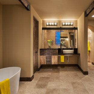 Ejemplo de cuarto de baño principal, de estilo americano, grande, con bañera exenta, armarios con paneles lisos, puertas de armario negras, paredes beige, suelo de travertino, lavabo sobreencimera, encimera de acrílico y suelo beige