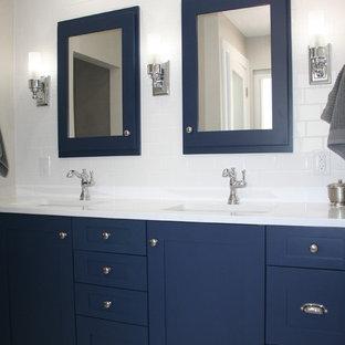 Klassisk inredning av ett badrum, med luckor med infälld panel, blå skåp, en dusch i en alkov, en toalettstol med separat cisternkåpa, vit kakel, keramikplattor, vita väggar, marmorgolv, ett undermonterad handfat, bänkskiva i kvarts, vitt golv och dusch med gångjärnsdörr