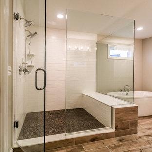 Diseño de cuarto de baño principal, rural, de tamaño medio, con bañera exenta, ducha esquinera, baldosas y/o azulejos blancos, baldosas y/o azulejos de cemento, paredes beige, suelo vinílico, suelo marrón y ducha con puerta con bisagras