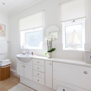 Beach style bathroom in London with white cabinets, white tiles, ceramic tiles, white walls, lino flooring, a built-in sink, laminate worktops and shaker cabinets.