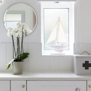 Exempel på ett litet maritimt badrum för barn, med luckor med infälld panel, vita skåp, en hörndusch, en toalettstol med hel cisternkåpa, vit kakel, keramikplattor, vita väggar, linoleumgolv, ett nedsänkt handfat och laminatbänkskiva