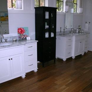 Ispirazione per una grande stanza da bagno padronale minimal con ante lisce, ante bianche, pareti gialle, parquet chiaro, lavabo sottopiano e top in marmo