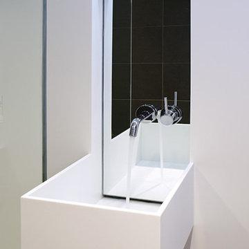 white corian and concrete bathroom