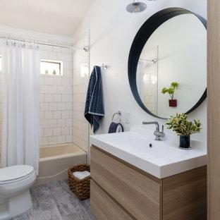 サンフランシスコの中くらいのトランジショナルスタイルのおしゃれなバスルーム (浴槽なし) (フラットパネル扉のキャビネット、中間色木目調キャビネット、アルコーブ型浴槽、シャワー付き浴槽、分離型トイレ、白いタイル、白い壁、一体型シンク、グレーの床、シャワーカーテン、白い洗面カウンター、洗面台1つ、フローティング洗面台) の写真