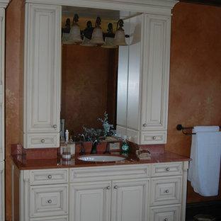 Foto de cuarto de baño principal, tradicional, grande, con armarios con paneles con relieve, puertas de armario blancas, parades naranjas, suelo de madera oscura, lavabo bajoencimera, encimera de ónix, suelo marrón y encimeras rojas