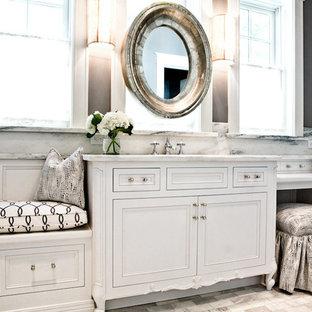 Immagine di una stanza da bagno classica di medie dimensioni con lavabo sottopiano, ante lisce, ante bianche, top in marmo, piastrelle bianche, lastra di pietra, pareti nere e pavimento in marmo