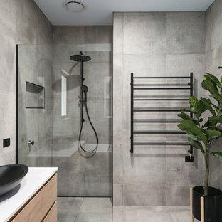 Immagine di una stanza da bagno padronale minimalista con ante lisce, ante beige, vasca freestanding, doccia alcova, piastrelle grigie, pareti grigie, lavabo a bacinella, pavimento grigio, porta doccia a battente, top bianco e pavimento in cemento