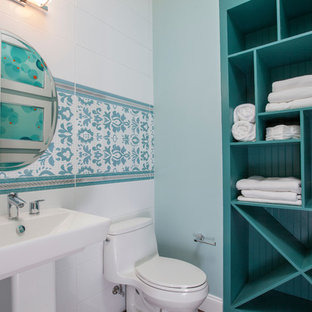 Small coastal bathroom photo in New York with open cabinets, a one-piece toilet, green walls, a pedestal sink and blue cabinets