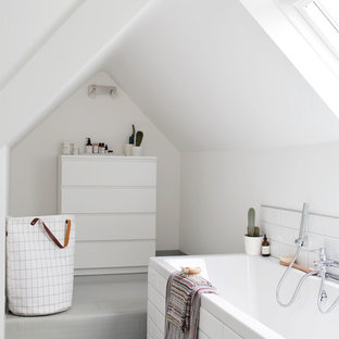 Photo of a medium sized contemporary ensuite bathroom in Gloucestershire with a built-in bath, white tiles, metro tiles, white walls and grey floors.