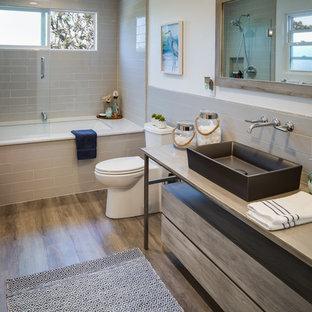 Выдающиеся фото от архитекторов и дизайнеров интерьера: ванная комната среднего размера в морском стиле с полновстраиваемой ванной, бежевой плиткой, серой плиткой, плиткой кабанчик, душевой кабиной, плоскими фасадами, серыми фасадами, душем над ванной, унитазом-моноблоком, паркетным полом среднего тона, настольной раковиной, коричневым полом, душем с раздвижными дверями и серой столешницей