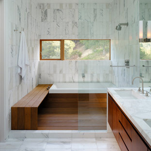 This is an example of a contemporary bathroom in San Francisco with a drop-in tub and flat-panel cabinets.