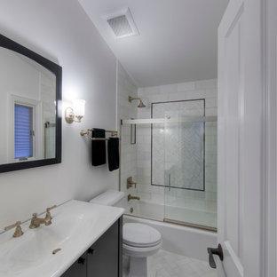 シカゴの中くらいのトラディショナルスタイルのおしゃれなマスターバスルーム (一体型シンク、フラットパネル扉のキャビネット、黒いキャビネット、人工大理石カウンター、アルコーブ型浴槽、シャワー付き浴槽、一体型トイレ、白いタイル、石タイル、白い壁、大理石の床) の写真
