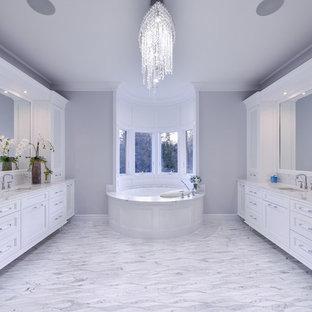 Ispirazione per una grande stanza da bagno padronale chic con ante con riquadro incassato, vasca idromassaggio, pareti grigie, pavimento con piastrelle in ceramica, lavabo sottopiano, pavimento grigio, top bianco e ante bianche
