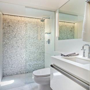 Idéer för ett litet modernt badrum med dusch, med ett undermonterad handfat, vita skåp, en dusch i en alkov, vit kakel, bänkskiva i akrylsten, en toalettstol med hel cisternkåpa, klinkergolv i porslin och släta luckor