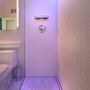 Ispirazione per una piccola stanza da bagno con doccia minimal con lavabo sottopiano, top in superficie solida, WC monopezzo, piastrelle bianche e pavimento in gres porcellanato