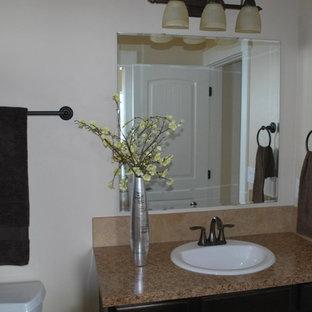 Idee per una stanza da bagno classica con lavabo da incasso, ante lisce, ante in legno scuro, top in laminato, WC a due pezzi, piastrelle beige, piastrelle di cemento, pareti beige e pavimento in linoleum