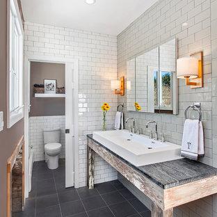 Imagen de cuarto de baño principal, rural, de tamaño medio, con lavabo de seno grande, puertas de armario con efecto envejecido, encimera de esteatita, baldosas y/o azulejos blancos, baldosas y/o azulejos de cemento, paredes grises, suelo de baldosas de porcelana y sanitario de dos piezas