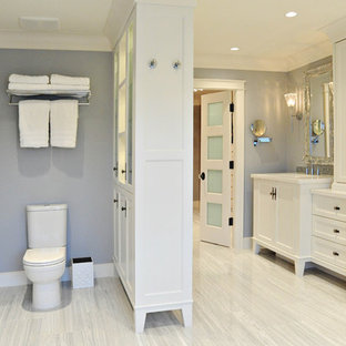 Freestanding bathtub - mid-sized traditional master white tile and stone tile marble floor freestanding bathtub idea in Vancouver with white cabinets, recessed-panel cabinets, a two-piece toilet, an undermount sink, engineered quartz countertops and gray walls