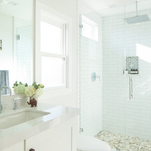 Small transitional 3/4 white tile and ceramic tile linoleum floor and turquoise floor alcove shower photo in Orange County with shaker cabinets, white cabinets, solid surface countertops, a two-piece toilet, white walls, an undermount sink and a hinged shower door