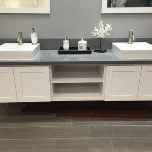 Неиссякаемый источник вдохновения для домашнего уюта: большая главная ванная комната в современном стиле с фасадами в стиле шейкер, белыми фасадами, серыми стенами, полом из ламината, накладной раковиной, столешницей из искусственного кварца, серым полом и серой столешницей