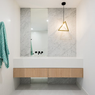 Photo of a mid-sized modern bathroom in Brisbane with light wood cabinets, a freestanding tub, white tile, gray tile, marble, marble floors, quartzite benchtops, an open shower, white benchtops, flat-panel cabinets, white walls, an integrated sink and grey floor.