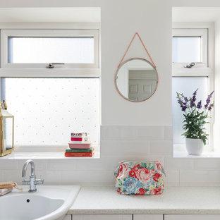 Inredning av ett lantligt litet badrum för barn, med skåp i shakerstil, vita skåp, ett platsbyggt badkar, en dusch/badkar-kombination, en toalettstol med hel cisternkåpa, vit kakel, tunnelbanekakel, vita väggar, laminatgolv, ett nedsänkt handfat och laminatbänkskiva