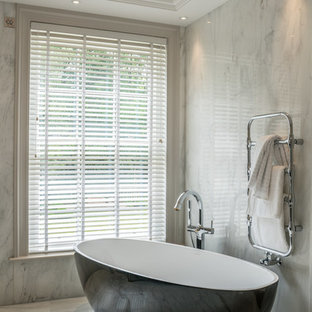 This is an example of a contemporary ensuite bathroom in Berkshire with a freestanding bath, grey tiles, stone slabs, grey walls and grey floors.