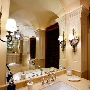 Huge mountain style master beige tile and stone tile travertine floor bathroom photo in Other with an integrated sink, raised-panel cabinets, white cabinets, granite countertops, a one-piece toilet and beige walls