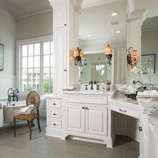Foto di una grande stanza da bagno padronale classica con lavabo sottopiano, ante con bugna sagomata, ante bianche, top in marmo, vasca con piedi a zampa di leone, pareti beige, pavimento con piastrelle in ceramica, piastrelle bianche e top grigio