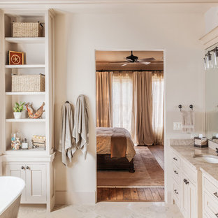 Inredning av ett lantligt beige beige en-suite badrum, med ett undermonterad handfat, skåp i slitet trä, ett fristående badkar, skåp i shakerstil, vita väggar, granitbänkskiva och beiget golv