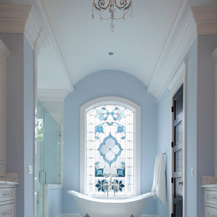 This is an example of a large traditional ensuite bathroom in Houston with a claw-foot bath, recessed-panel cabinets, white cabinets, an alcove shower, white tiles, blue walls, marble flooring, marble worktops, white floors, a hinged door and white worktops.