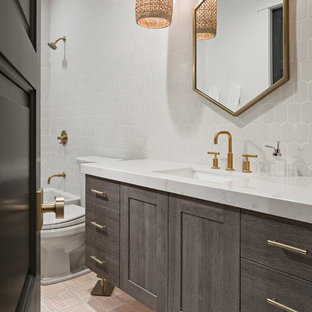 Large traditional family bathroom in Phoenix with flat-panel cabinets, grey cabinets, an alcove bath, a walk-in shower, a one-piece toilet, white tiles, ceramic tiles, white walls, cement flooring, a submerged sink, engineered stone worktops, pink floors and a shower curtain.