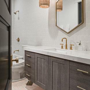 Пример оригинального дизайна интерьера: большая детская ванная комната в стиле современная классика с плоскими фасадами, серыми фасадами, ванной в нише, открытым душем, унитазом-моноблоком, белой плиткой, керамической плиткой, белыми стенами, полом из цементной плитки, врезной раковиной, столешницей из искусственного кварца, розовым полом и шторкой для душа