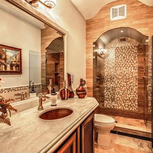 Foto di una stanza da bagno mediterranea di medie dimensioni con lavabo sottopiano, ante con bugna sagomata, ante in legno scuro, top in granito, WC monopezzo, piastrelle beige, piastrelle di vetro, pareti beige e pavimento in travertino