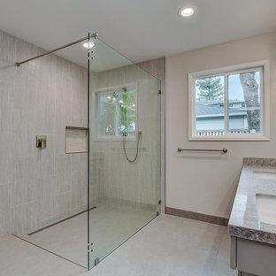 Inredning av ett modernt stort grå grått en-suite badrum, med luckor med infälld panel, grå skåp, en kantlös dusch, en toalettstol med hel cisternkåpa, grå kakel, keramikplattor, grå väggar, klinkergolv i keramik, ett nedsänkt handfat, bänkskiva i kvartsit, grått golv och dusch med gångjärnsdörr