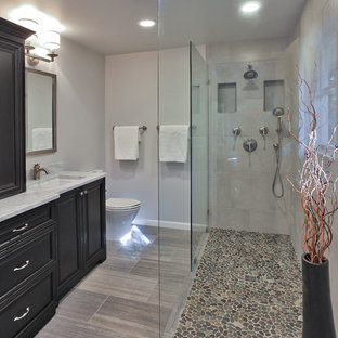 Example of a mid-sized transitional master gray tile and porcelain tile porcelain tile doorless shower design in DC Metro with an undermount sink, dark wood cabinets, marble countertops, a two-piece toilet, gray walls and recessed-panel cabinets