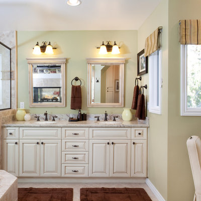 Bathroom - mid-sized traditional master porcelain tile ceramic tile and beige floor bathroom idea in San Diego with raised-panel cabinets, white cabinets, solid surface countertops, an undermount sink, beige walls and a hinged shower door