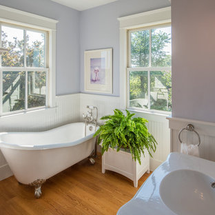 Example of a farmhouse medium tone wood floor and brown floor claw-foot bathtub design in DC Metro with purple walls, an integrated sink and white countertops