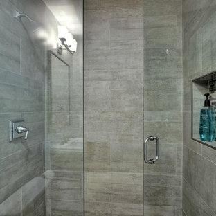 Bild på ett mellanstort vintage badrum med dusch, med en dusch i en alkov, grå kakel, dusch med gångjärnsdörr, en toalettstol med separat cisternkåpa, ett piedestal handfat, grått golv, kaklad bänkskiva, keramikplattor, grå väggar och klinkergolv i keramik