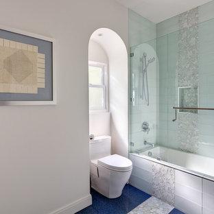 Bild på ett litet funkis badrum, med luckor med infälld panel, vita skåp, en dusch/badkar-kombination, en toalettstol med hel cisternkåpa, glaskakel, vita väggar, ett undermonterad handfat, bänkskiva i kvartsit, ett platsbyggt badkar, dusch med gångjärnsdörr, klinkergolv i porslin och blått golv