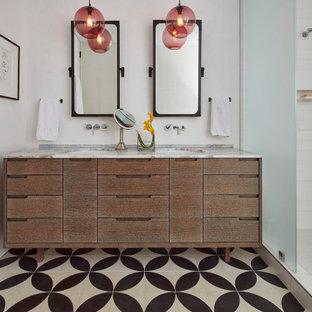 Aménagement d'une salle de bain rétro avec un placard à porte plane, des portes de placard en bois brun, un carrelage blanc, un mur blanc, un sol en carreaux de ciment, un lavabo encastré, un sol multicolore, aucune cabine, un plan de toilette blanc et meuble double vasque.