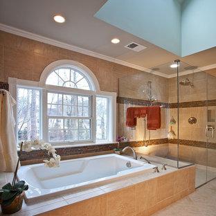 ローリーの大きいトランジショナルスタイルのおしゃれなマスターバスルーム (シェーカースタイル扉のキャビネット、中間色木目調キャビネット、ドロップイン型浴槽、段差なし、分離型トイレ、ベージュのタイル、テラコッタタイル、グレーの壁、トラバーチンの床、アンダーカウンター洗面器、珪岩の洗面台) の写真