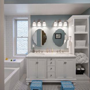 Modelo de cuarto de baño infantil, clásico, pequeño, con armarios tipo mueble, puertas de armario blancas, bañera empotrada, combinación de ducha y bañera, sanitario de dos piezas, baldosas y/o azulejos blancos, baldosas y/o azulejos de cemento, paredes azules, suelo con mosaicos de baldosas, lavabo bajoencimera y encimera de mármol