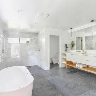 Idéer för ett stort modernt vit en-suite badrum, med släta luckor, vita skåp, ett fristående badkar, en dubbeldusch, en toalettstol med separat cisternkåpa, grå kakel, vit kakel, marmorkakel, vita väggar, skiffergolv, ett undermonterad handfat, grått golv och med dusch som är öppen
